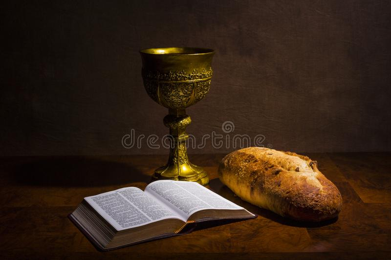 Chalice with wine bread and Holy Bible on a table stock photo