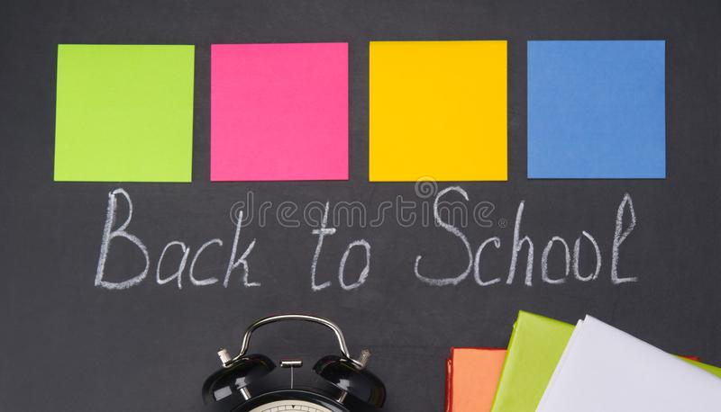 Chalk on the blackboard, back to school, a set of multicolored stickers for recording on them, and a black alarm bell royalty free stock photo