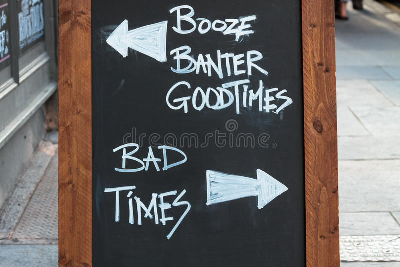 Chalk board with good times versus bad times. Chalk board in front of a pub with good times versus bad times royalty free stock photos