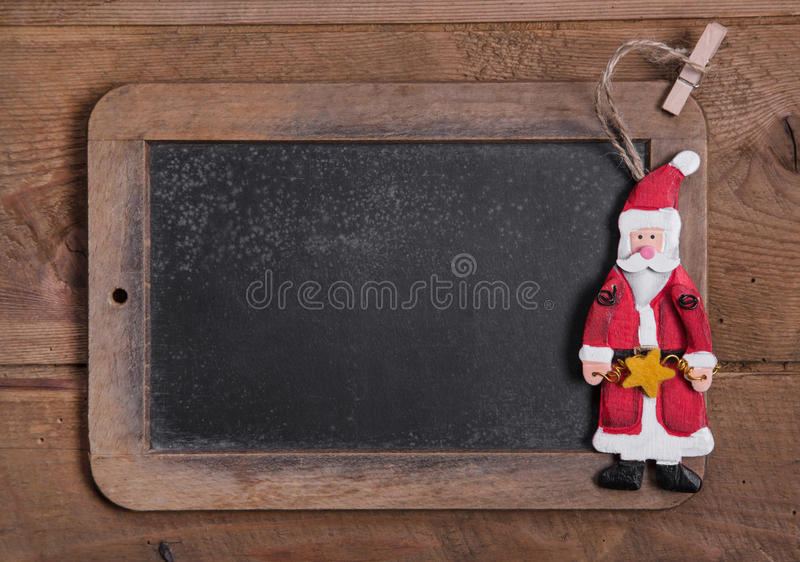 Chalk board for Merry Christmas message , santa on wooden background for a greeting card royalty free stock photography