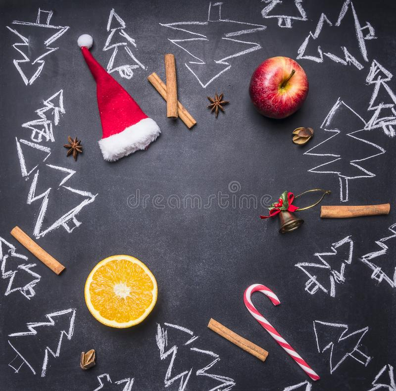 Chalk board with painted Christmas decorations, Christmas trees, candy, cups and ingredients for mulled wine, frame, space f royalty free stock photography