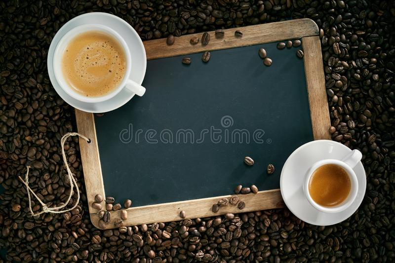 Chalk board or slate with cups of coffee and beans royalty free stock photos