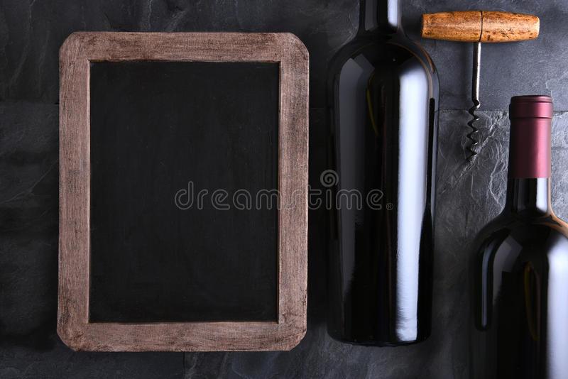 Chalk Board and Wine Bottles. Top view of a blank chalk board for a wine list or menu with two wine bottles and old cork screw. Side light on a slate table royalty free stock photo