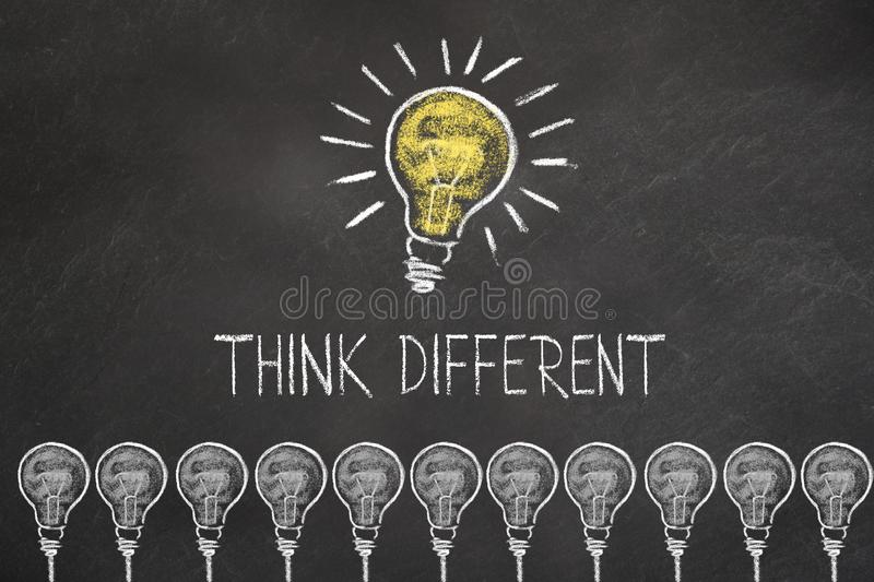Chalk bulb idea on a blackboard with text `think different` royalty free illustration