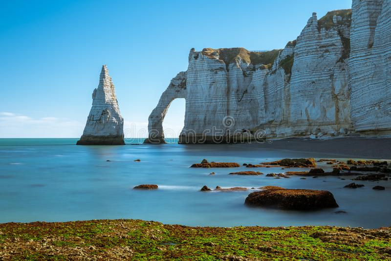 Chalk cliffs of Etretat with the natural arch Porte d`Aval and the stone needle called L`Aiguille. Chalk cliffs of Etretat Normandy France with the natural arch stock images