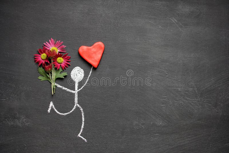 Chalk drawing man with bouquet of flowers and big red heart on chalkboard background with copy space. Valentines day gift or stock images