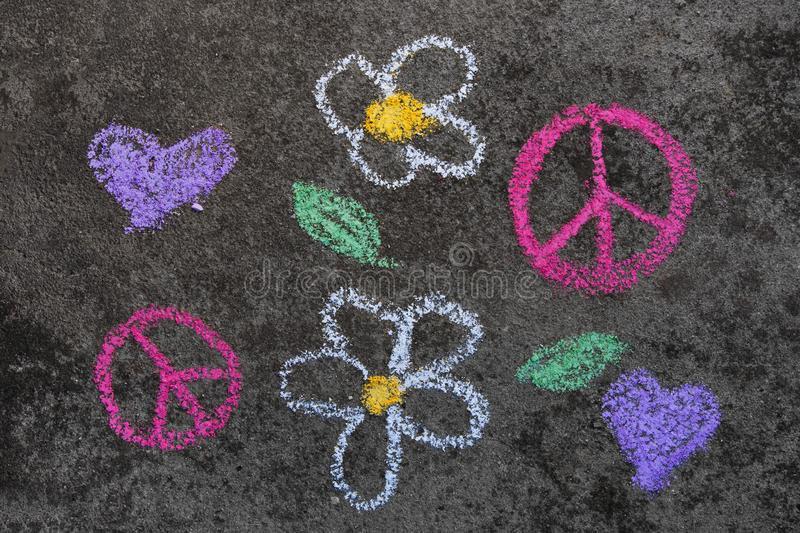 Chalk drawing: Pink peace symbol and beautiful flowers stock photography