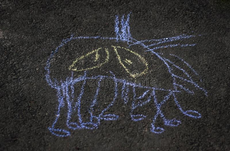 A chalk picture on a road. Kids art. Funny monster, sad spider. Kids art drawing on a road stock image