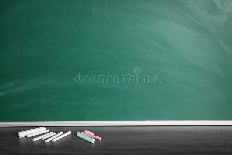 Chalk sticks on table near board royalty free stock images