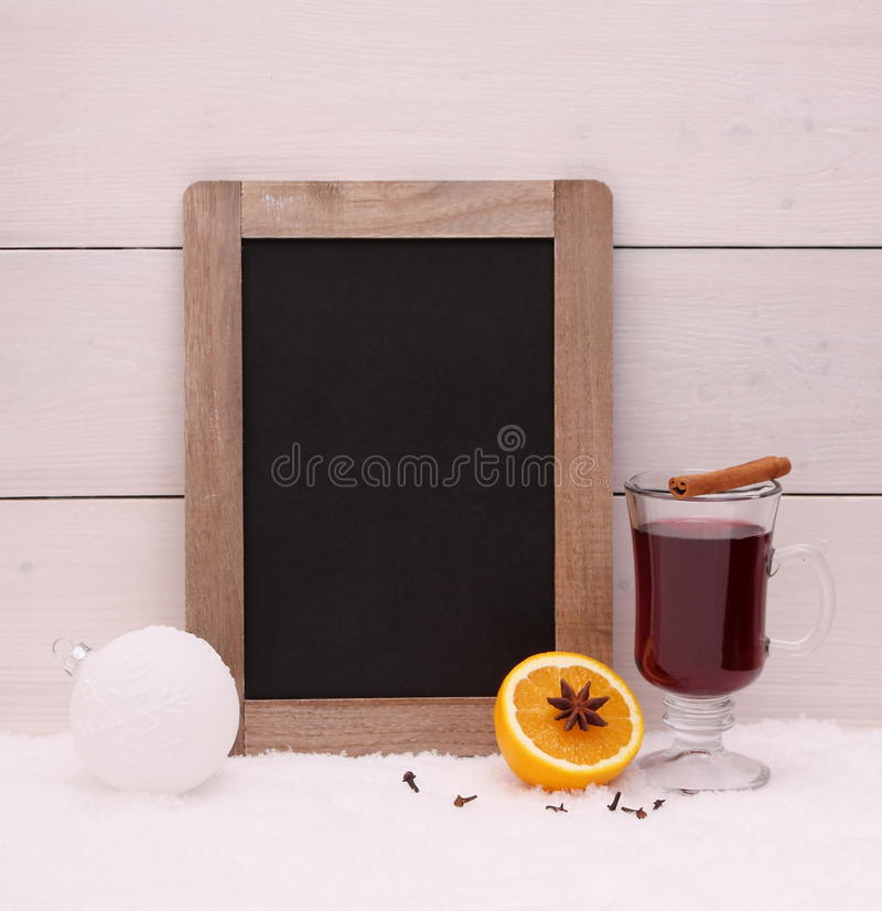 Chalk writing board, mulled wine, orange. And spice on snow stock image