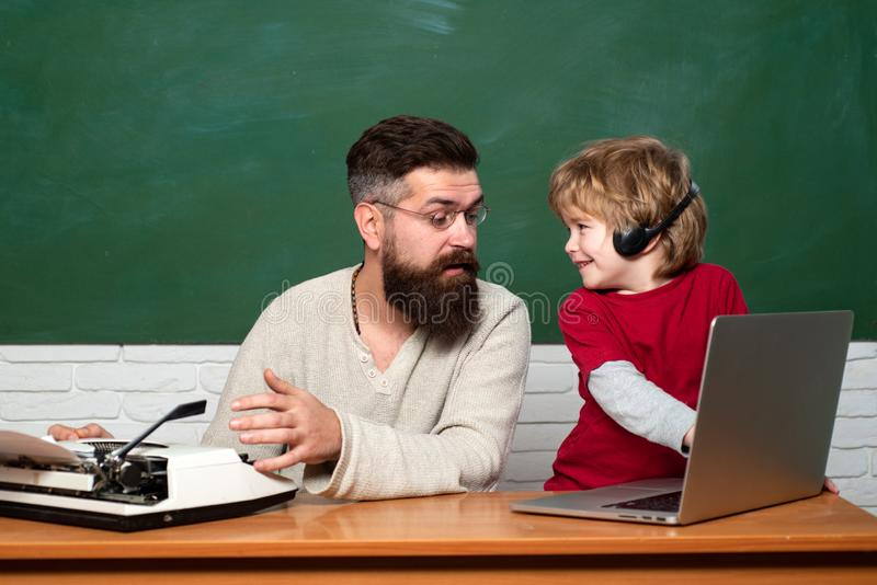 Chalkboard background. Homeschooling. First day in school. Parent Teacher. father teaching her son in classroom at. School. Teacher helping young boy with royalty free stock photo