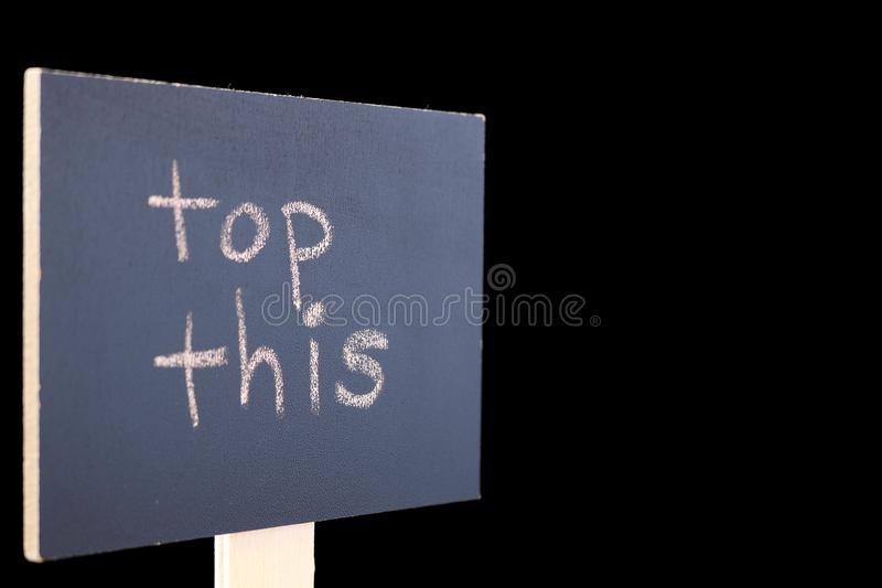 Top This - chalkboard sign on black background. Chalkboard or blackboard sign with `top this` text - good for social media posts, blogs, internet publishing royalty free stock photos