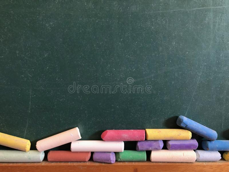 Blank chalkboard with coloured chalks stock photos