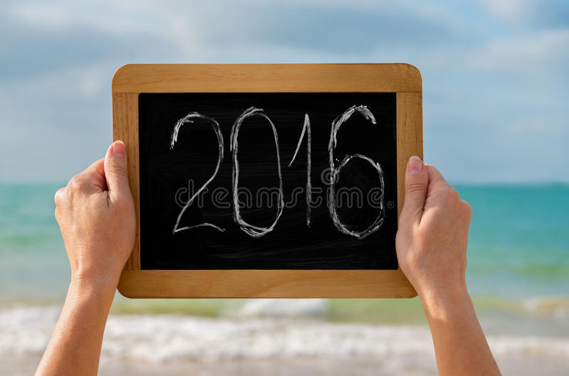 Chalkboard and digits 2016. Womans hands with chalkboard and digits 2016 on it against the sea - concept of new year, vacation and travel stock photo