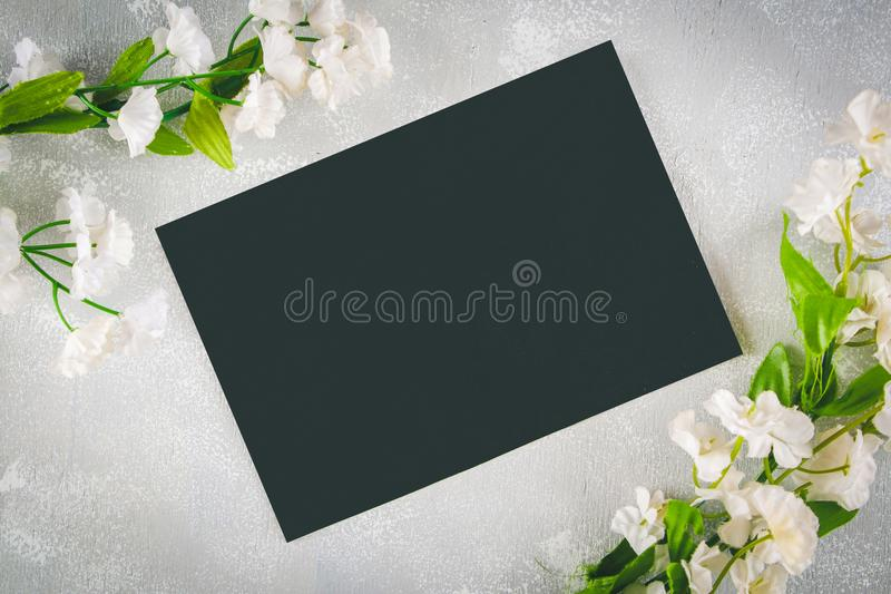 Chalkboard with an empty field surrounded by white flowers on a gray background. Copy the space. Template for spring or female hol royalty free stock images