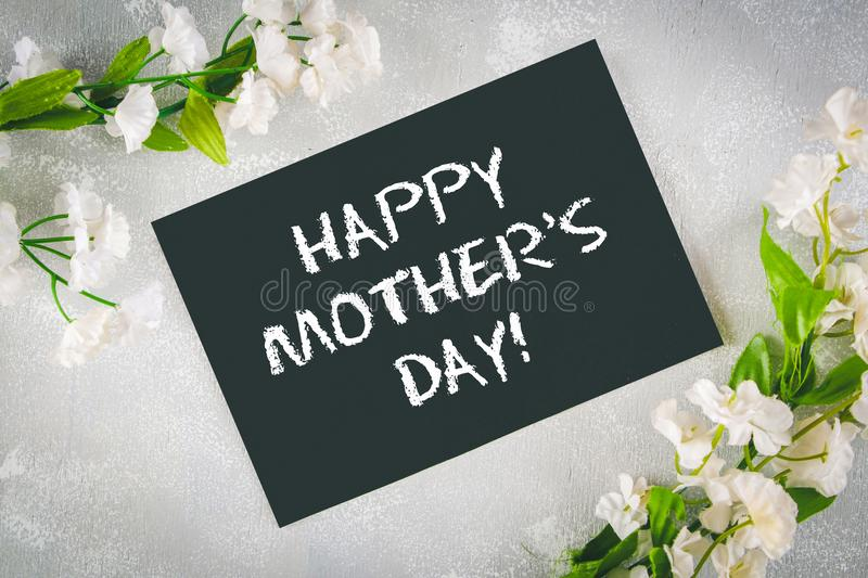 Chalkboard with an empty field surrounded by white flowers on a gray background. Happy mother`s day. royalty free stock images