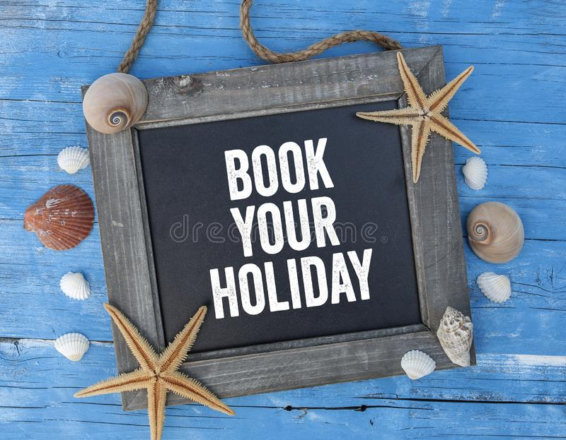 Chalkboard with maritime decoration on blue wooden background with Book your Holiday. Chalkboard with maritime decoration on blue wooden background stock photo