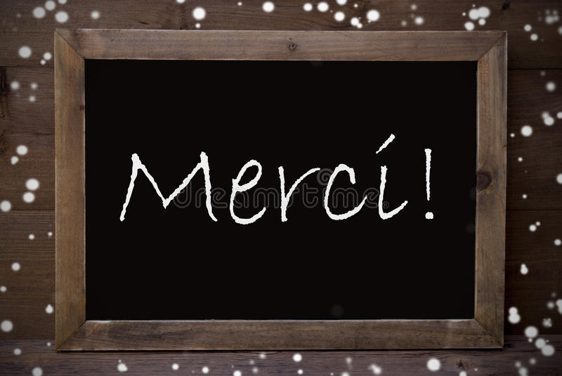 Chalkboard With Merci Means Thank You, Snowflakes. Brown Blackboard With French Text Merci Means Thank You As Greeting Card. Wooden Background. Vintage Rustic stock photos