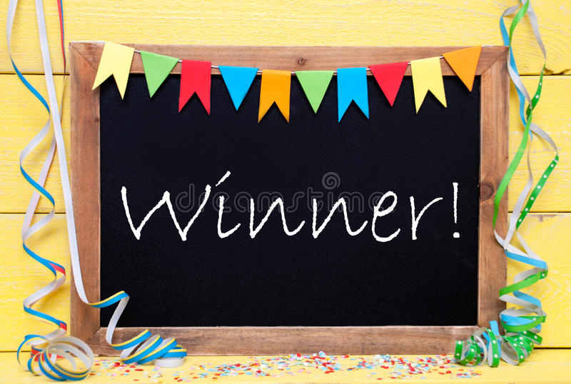 Chalkboard With Party Decoration, Text Winner. Chalkboard With English Text Winner. Party Decoration Like Streamer, Confetti And Bunting Flags. Yellow Wooden stock photo