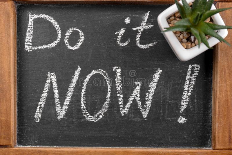 Chalkboard with phrase \'Do it now\', closeup. Time management concept stock image
