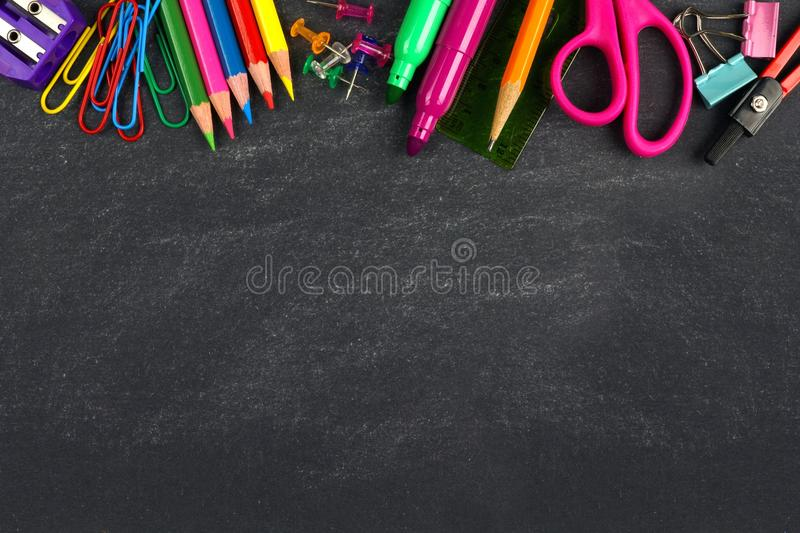 Chalkboard with school supplies top border stock image