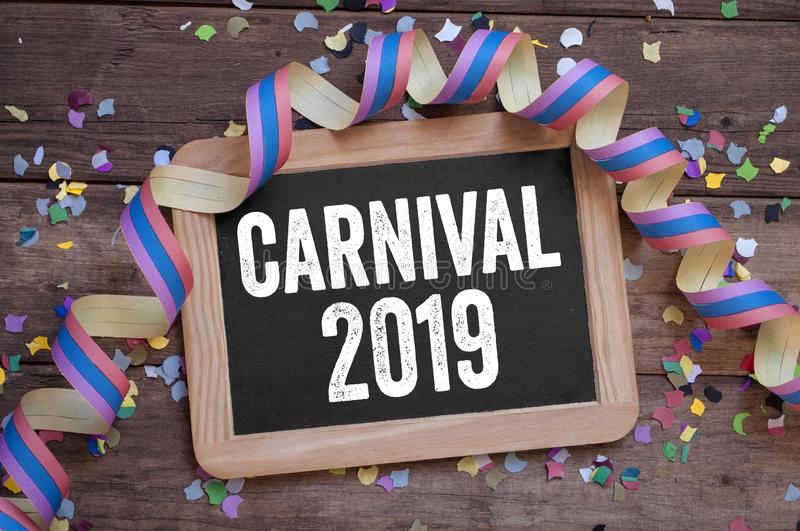 Chalkboard with streamers, confetti on wooden background with carnival 2019 royalty free stock image