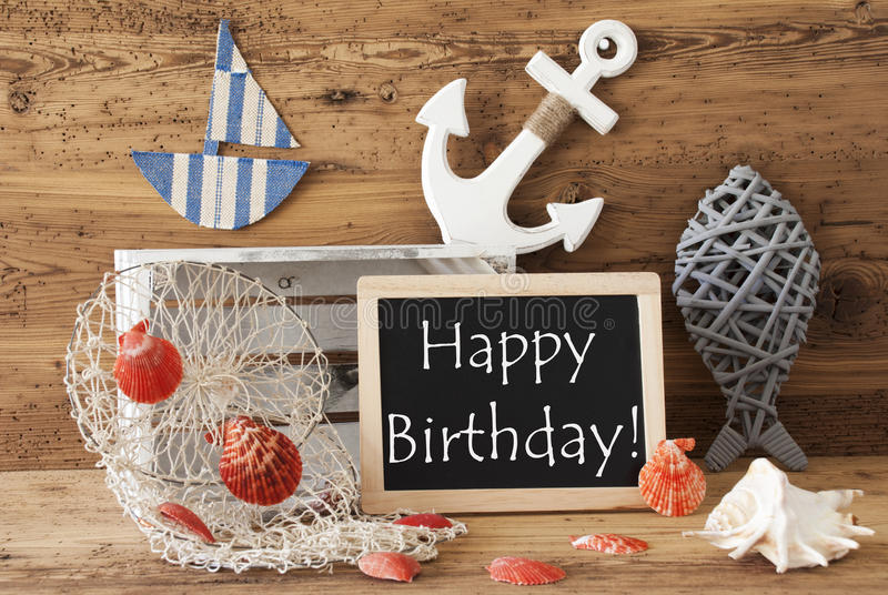 Chalkboard With Summer Decoration, Text Happy Birthday. Blackboard With Nautical Summer Decoration And Wooden Background. English Text Happy Birthday. Fish royalty free stock image