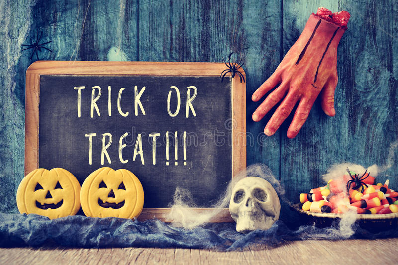 Chalkboard with the text trick or treat in a halloween scene royalty free stock photos