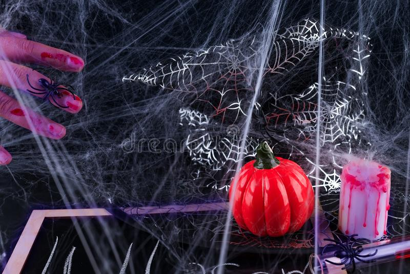 Spooky Halloween Background with bloody hands, pumpkins, cobwebs, spiders on black stock photos