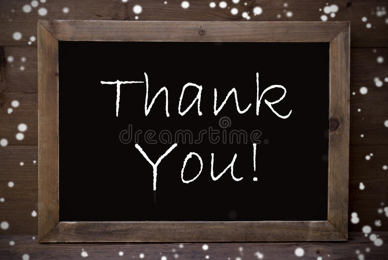 Chalkboard With Thank You, Snowflakes. Brown Blackboard With English Text Thank You As Greeting Card. Wooden Background. Vintage Rustic Style. Snowflakes royalty free stock photo