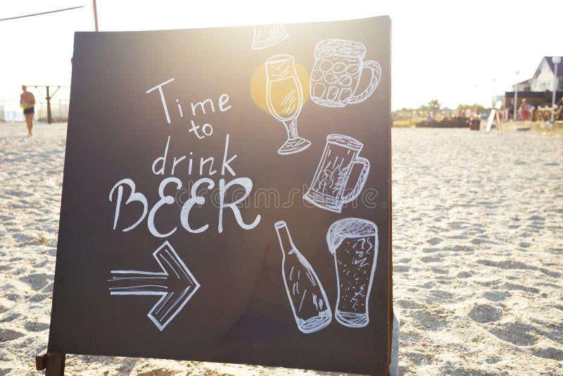 Chalkboard w słońce promieniach na plaży z tekstem: Czas pić obrazy royalty free