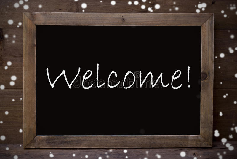 Chalkboard With Welcome, Snowflakes. Brown Blackboard With English Text Welcome As Greeting Card. Wooden Background. Vintage Rustic Style. Snowflakes Symbolizing royalty free stock photos