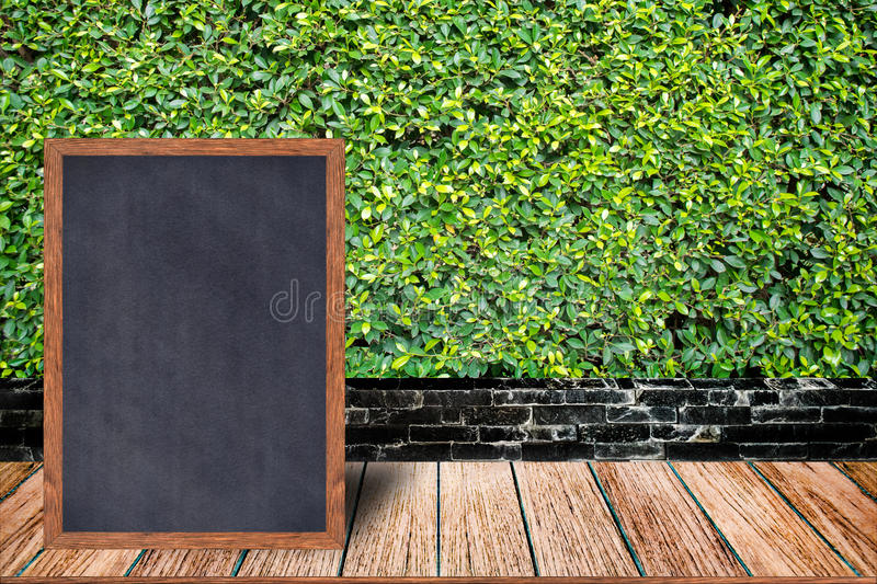 Chalkboard wood frame, blackboard sign menu on wooden table and grass wall background. Chalkboard wood frame, blackboard sign menu on wooden table and grass stock photo