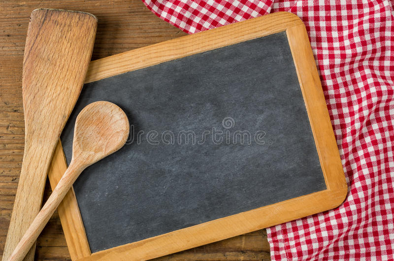 Chalkboard with wooden spoons on a red checkered tablecloth stock photography