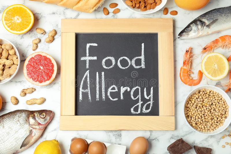 Chalkboard with words FOOD ALLERGY and different products on white marble table. Flat lay royalty free stock image