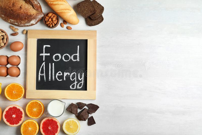 Chalkboard with words FOOD ALLERGY and different products on white table. Space for text. Chalkboard with words FOOD ALLERGY and different products on white stock images