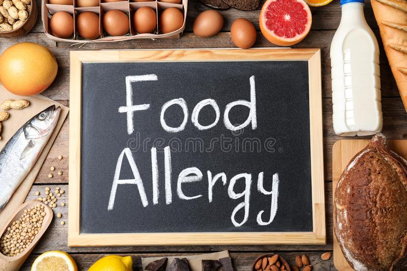 Chalkboard with words FOOD ALLERGY and different products on wooden table. Flat lay stock photo
