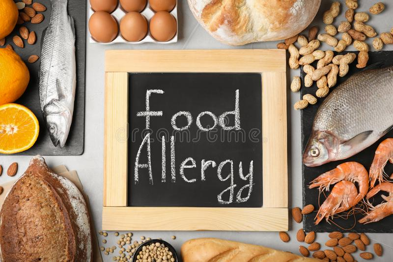 Chalkboard with words FOOD ALLERGY and groceries on grey table stock photography