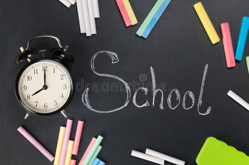 On the chalkboard written word school around lies a multi-colored chalk and the clock lies royalty free stock images