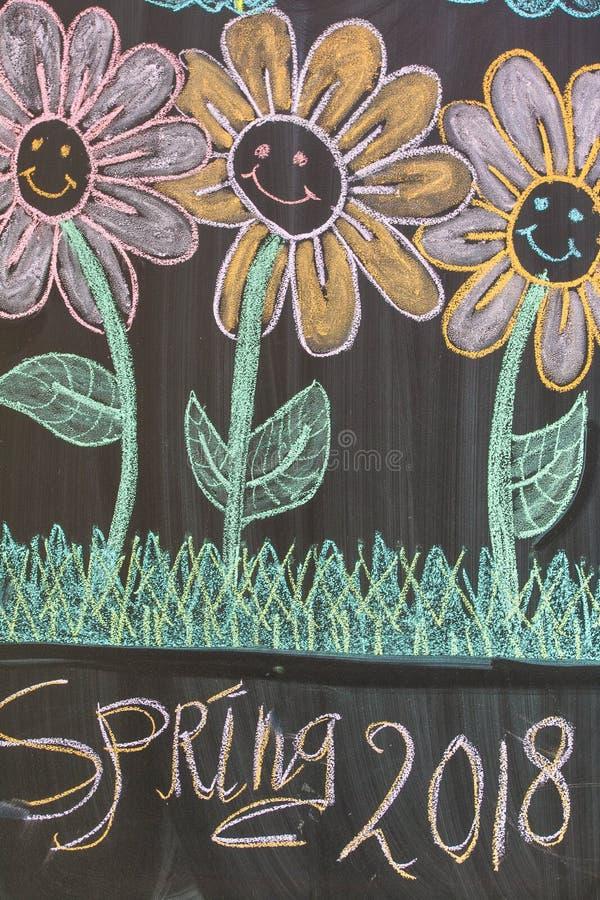 Chalkboard z dziecka rysunkowego colorfull szczęśliwymi kwiatami z tekst wiosną 2018 obraz royalty free