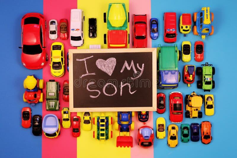 Chalkboard z inskrypcją kocham mój syna, otaczającego barwionymi samochodami na stubarwnym tle zdjęcia stock