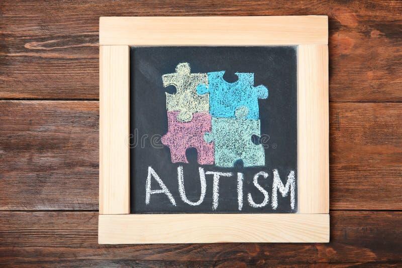 Chalkboard z słowem autyzm i rysujący łamigłówka kawałki fotografia stock