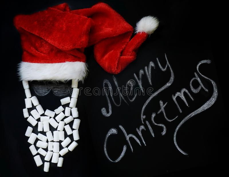 Chalked Santa Claus with a real red cap and a marshmallow beard on a chalkboard and a chalk inscription Merry Christmas . new year. Halked Santa Claus with a stock photography