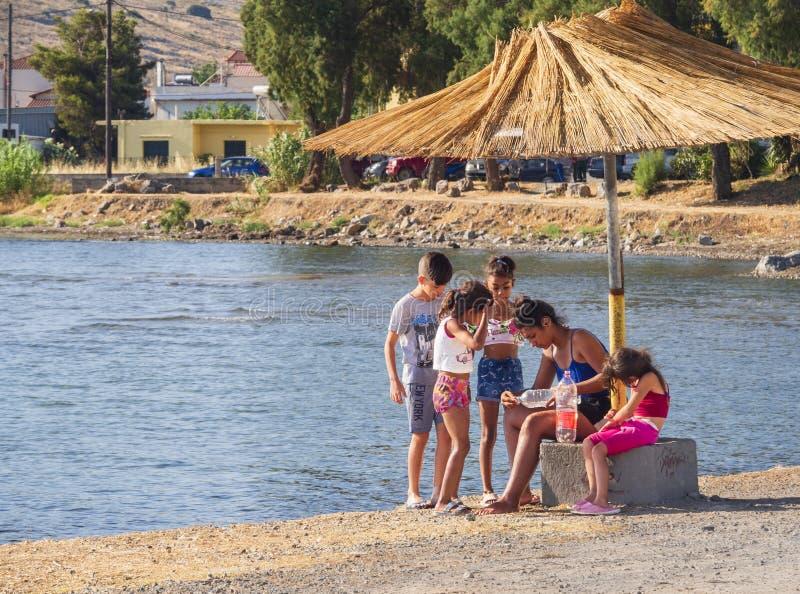 Chalkida, isola di Evia Luglio 2019: Vista panoramica della spiaggia della città delle munizioni di Liani con i turisti ed i bamb fotografia stock libera da diritti