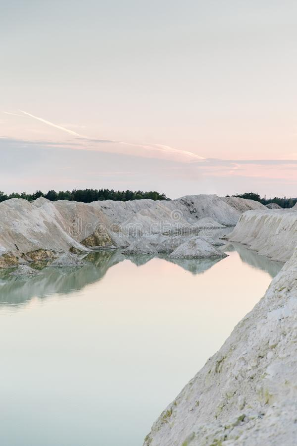 Mountain lake with crystal clear water. Chalky quarries - emerald blue water, vanilla sunset, white stones, pink sunset royalty free stock image
