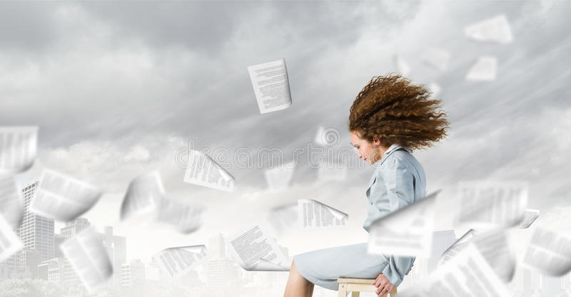 Challenge in business. Young tired businesswoman with waving hair among flying documents stock photo