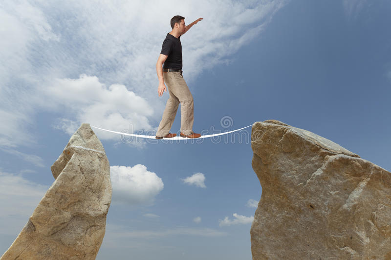 Challenge concept. Man walking on wire. Man walking on wire between two boulders. Challenge concept: difficult royalty free stock photography