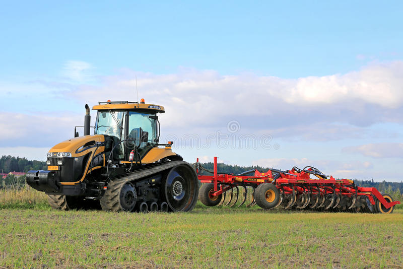 Challenger MT765C Tracked Agricultural Tractor and Cultivator. SALO, FINLAND -SEPTEMBER 6, 2014: Challenger MT765C tracked agricultural tractor and cultivator on stock image