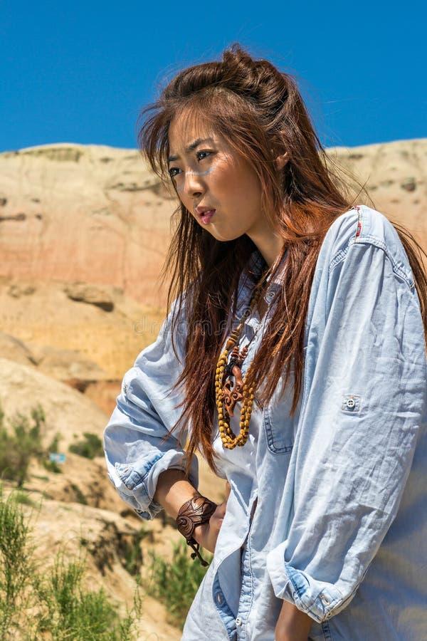 Chamán asiático de la muchacha en un fondo de montañas en el desierto imágenes de archivo libres de regalías