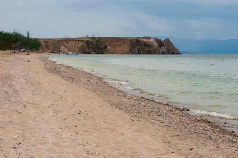 Chamán Rock en el lago Baikal en tiempo melancólico Orilla de mar espumosa Hay un barco cerca de la orilla fotos de archivo